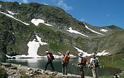 A group of walkers trekking around a mountain lake in Bulgaria