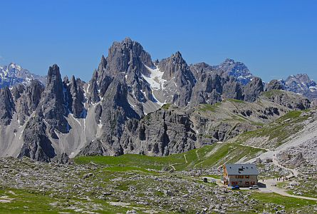 Amazing rocky peaks of the Dolomites with a mountain hut and walkers in the foreground