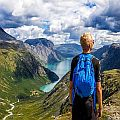 Hiker admiring a beautiful landscape of high mountains and a fjord at the bottom
