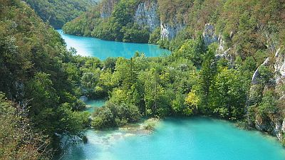 Azure blue lakes within a forested landscape in Plitvice Lakes National Park in Croatia.