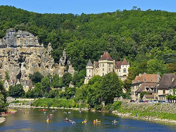 People canoeing on the Dordogne river with castle and limestone cliffs in the background.
