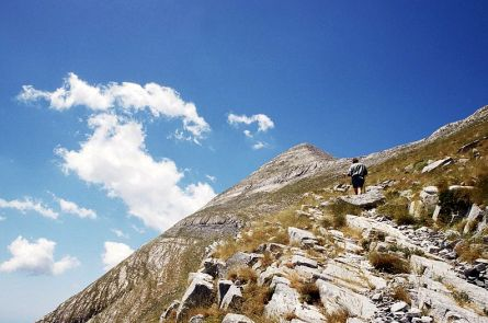 Steep mountain peak with rocky slopes in Greece and a walker looking at the peak.