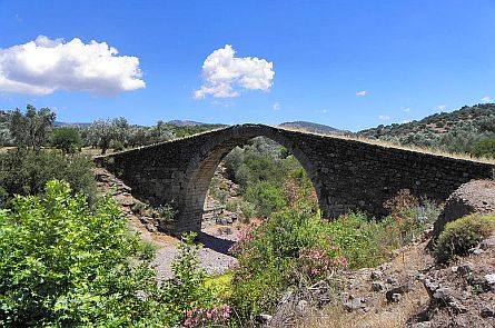 Ancient rounded bridge over a stream in a Mediterranean landscape on the Greek island of Lesbos (Lesvos).