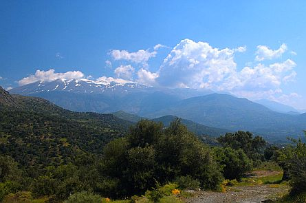 View on very high mountains with snow patches and beautiful clouds, and a green Mediterranean spring landscape in the foreground.