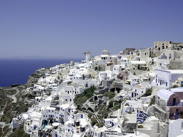 White washed houses on a hill sloping down to the sea.