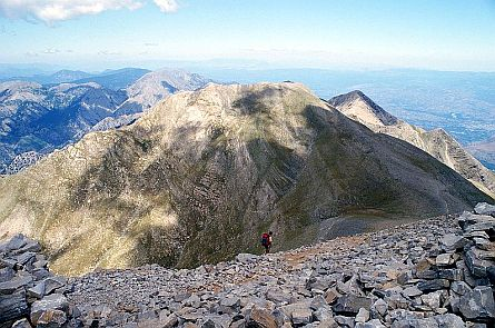 Panoramic view on a extensive mountain range with a walker in the foreground.