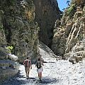 View on deep rocky gorge with two people walking in the foreground.