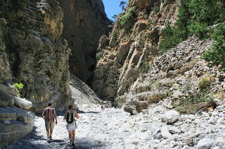 Two people walking through a rocky landscape, just before they enter a narrow gorge.
