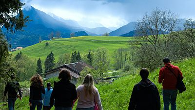 Group of walkers walking down a a hill in Austria in early Spring. Green pastures and high blueish mountains in the background. Original photo by Ralph Unden (see http://www.flickr.com/photos/ralphunden/2494603451/)