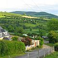 View on green and lush Ireland countryside with a house and road leading off in the distance.