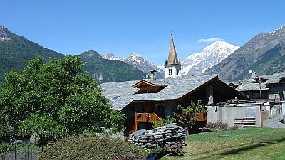 View on wooden chalet and church tower in small village with snowcapped Mont Blanc mountains in the background.