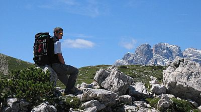 A walker taking a break during a walking holiday in the Italian Alps.