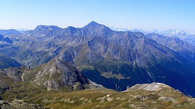 Panoramic view on part of the Cottian Alps in Italy, with green valleys and slopes and bare upper slopes.