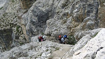 A steep rocky path with support cables and two climbers ascending.