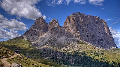 View on steep pinnacles and peaks of the Dolomites with two walkers and a walking path in the left foreground.