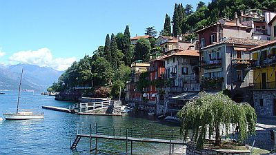 View on one of the Italian Lakes, lake Como, with a small boat in the water, a jetty and houses on the shore.