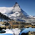 View on the Matterhorn with an Alpine lake and some walkers in the foreground.