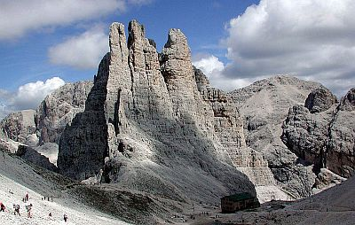Impressive landscape in the Dolomites, with a mountain refuge and walkers and hikers in the foreground.