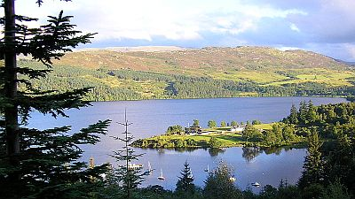 View on a Scottish loch with hills and moorland in the back and small boats on the loch. Original photo http://commons.wikimedia.org/wiki/File:Great_Glen_Way_-_View_of_Loch_Ness_from_Fort_Augustus.JPG
