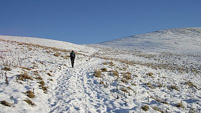 A lone walker walking up a gentle slope in a snowy landscape. Original photo http://commons.wikimedia.org/wiki/File:Walking_in_the_Cheviot_Hills_-_geograph.org.uk_-_1636989.jpg.