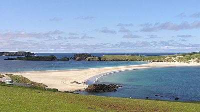 View on green cliffs and a sandbank in a beautiful bay on the Shetland isles in Scotland. Original photo http://commons.wikimedia.org/wiki/File:Tombolo_St_Ninians_5940.JPG