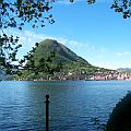 The Swiss city of Lugano at the foot of a mountain seen from the shore of Lake Lugano.