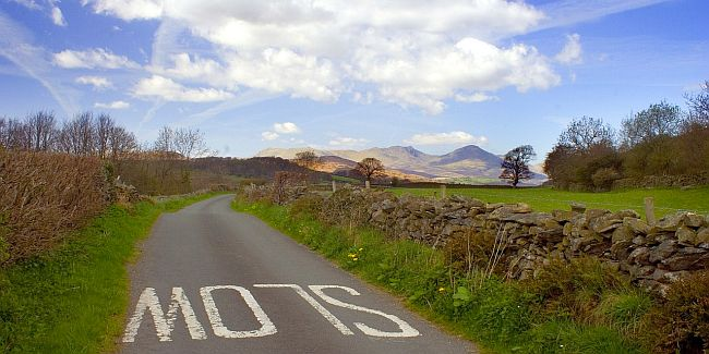 Road in the UK lake district with the word SLOW written on it.