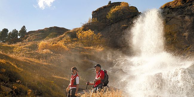 A pair of walkers hiking a steep hill.