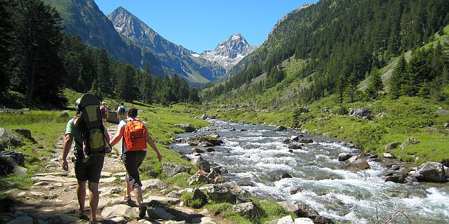 Group of walkers hiking along a mountains stream.