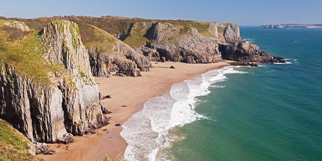View on stunning beach framed by steep cliffs and the deep blue sea.