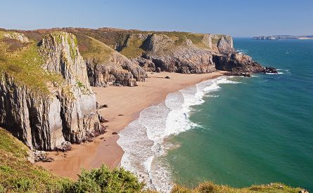 View on stunning beach with high cliffs in Pembrokeshire