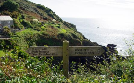 Photo of coast path sign with view on the coast and sea behind