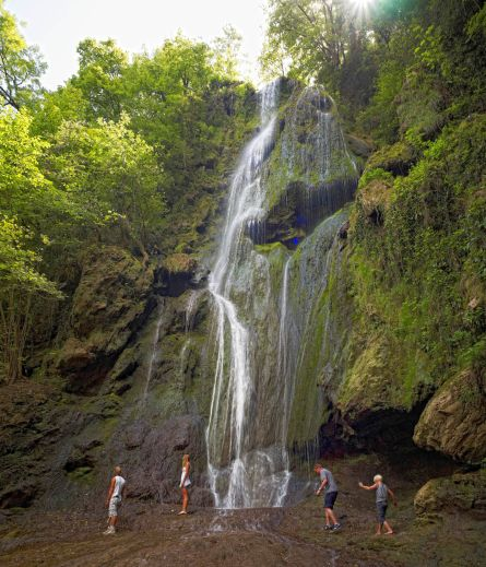 People walking below a waterfall near Autoire