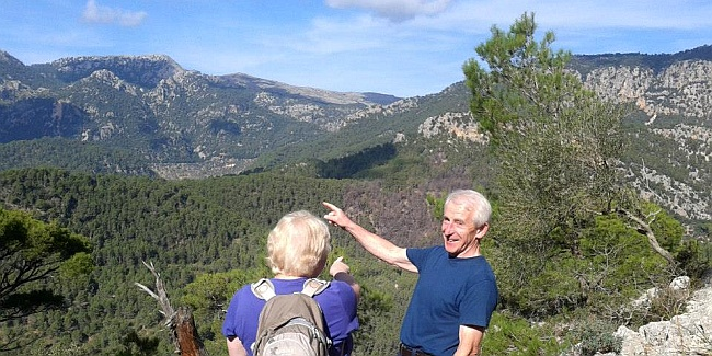 Elderly couple pointing towards mountains