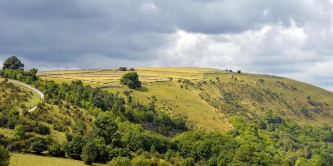 Grey clouds over a hillside walking trail