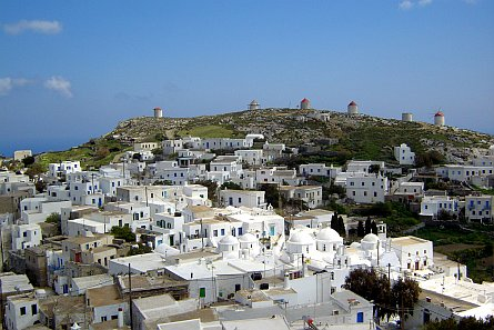 Greek village with whitewashed houses and windmills on a hillside