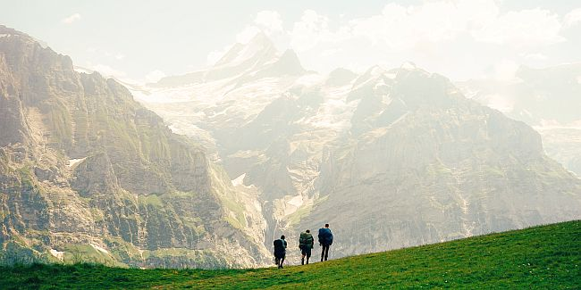 Group of 3 friends hiking over a grassy meadow in high mountains