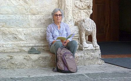 Woman with tourist guide and backpack sitting against an old stone wall