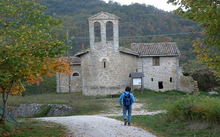 Person walking towards a medieval chapel in Roman style