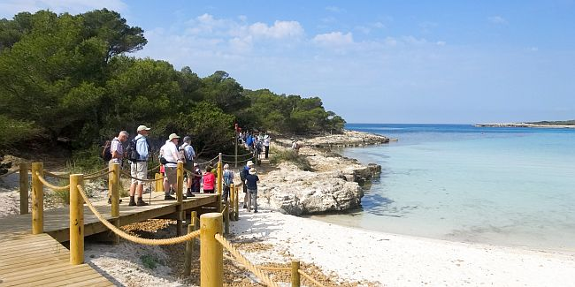 Group of walkers at the Menorca coast, following a track past an empty beach