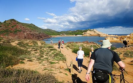 Diverse group of hikers following a sand path to a blue bay