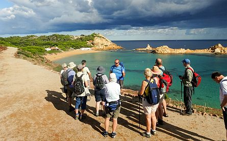 Walking guide in front of a group, overlooking a bay on Menorca