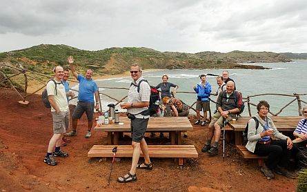 Walkers and hikers at a picnic table overlooking the sea, waving hello