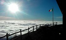 Italian flag on a high mountain top,sun above and clouds beneath