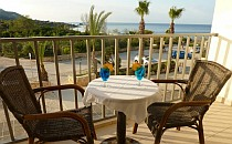 Two chairs and a table with two coctail glasses on a terrace with a view of the sea