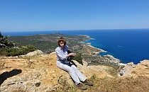 Lady sitting on a rock, magnificent view of an island going into the blue sae