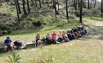 Group of hikers sitting on a short stone wall