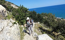 People walking on a rocky trail, view of the blue sea in the background