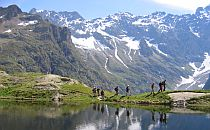 Group of climbers with a guide walking past a lake towards high snow-capped mountains in the background