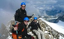 Three climbers on the summit of a snow-capped mountain in the French Alps.